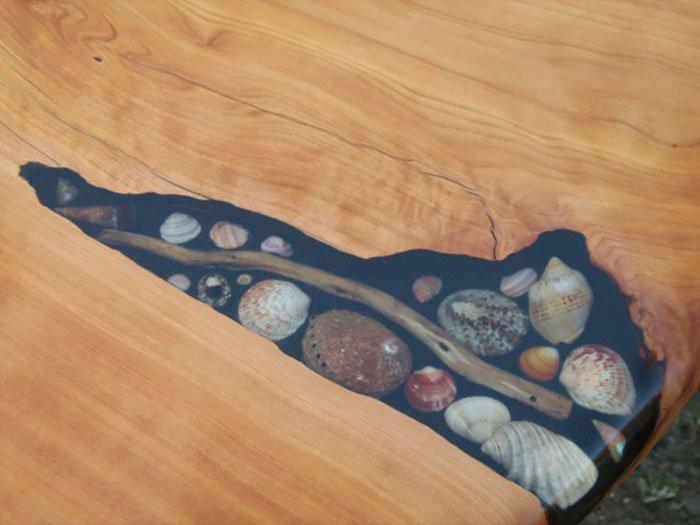 Художники заполняют трещины в столах ракушками, камешками и морскими звёздами